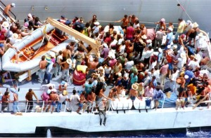 FILE-In this Aug. 24, 1994 file photo, more than one hundred Cuban refugees await to disembark onto a U.S. Naval warship from the Coast Guard Cutter Baronof about 50 miles south of the coast of Key West, Fla.  (AP Photo/Hans Deryk, File)