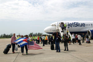 Passengers of a JetBlue aeroplane, the first commercial scheduled flight between the United States and Cuba in more than 50 years, carry U.S. and Cuban national flags after it landed at the Abel Santamaria International Airport in Santa Clara, Cuba, August 31, 2016. REUTERS/Alexandre Meneghini
