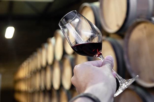 https://www.freepik.com/premium-photo/closeup-hand-with-glass-red-wine-background-wooden-oak-barrels-stacked-straight-rows-order-old-cellar-winery_5426986.htm#query=wine%20store&position=14