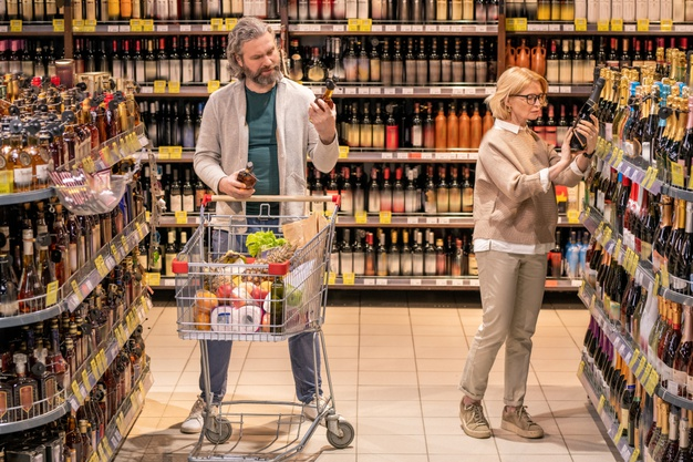 https://www.freepik.com/premium-photo/mature-bearded-man-with-shopping-cart-choosing-bottle-cognac-by-shelf-alcohol-department-while-his-wife-taking-champagne_11344426.htm